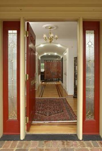A wide doorway without a threshold leads into the open foyer, creating a dramatic and easily accessible entryway. The barrel-vaulted hallway beyond is wide enough for two wheelchairs to pass side-by-side.