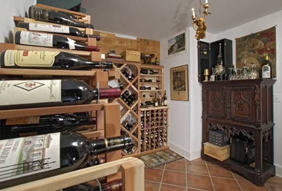 "The above ground wine ""cellar,"" a climate-controlled room with built-in shelving, was the couple's innovative solution for wine storage."