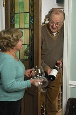 Rick Barry and Linda Cox select a wine from the extensive collection stored in their wine room. An antique door featuring a stained glass panel separates the wine room from the formal dining room.
